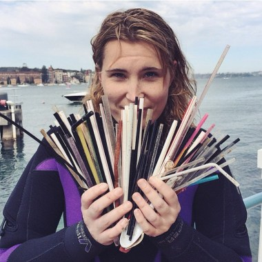 A diver holds the stash of over 100 plastic straws found underwater